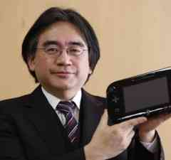 Nintendo Co's President Iwata poses with company's Wii U gaming controller at company headquarters after an interview with Reuters in Kyoto
