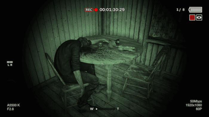 A screenshot from Outlast 2. A body lies slumped over a table.