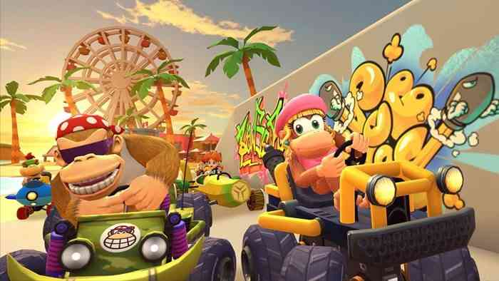 Funky Kong and Dixie Kong are riding Go-Karts past a graffiti covered cement wall with palm trees and a Ferris Wheel in the background.