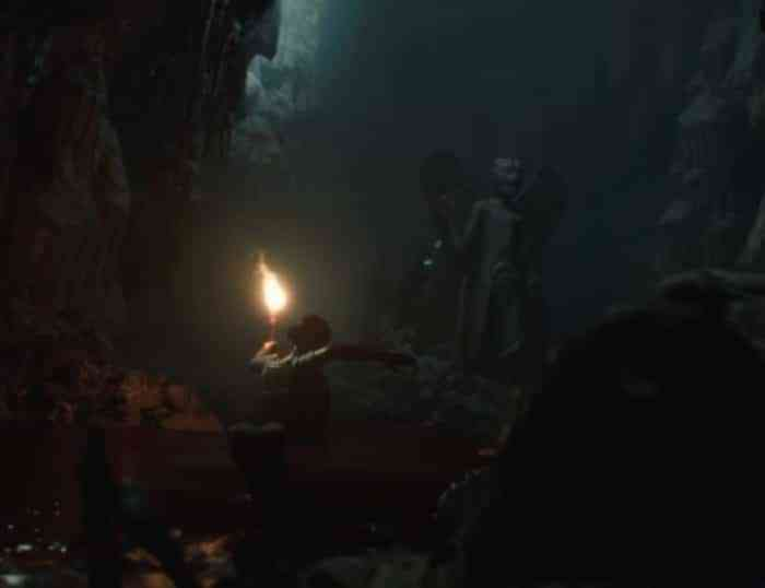 A screenshot of a character wandering through an underground tomb with a torch from House of Ashes.