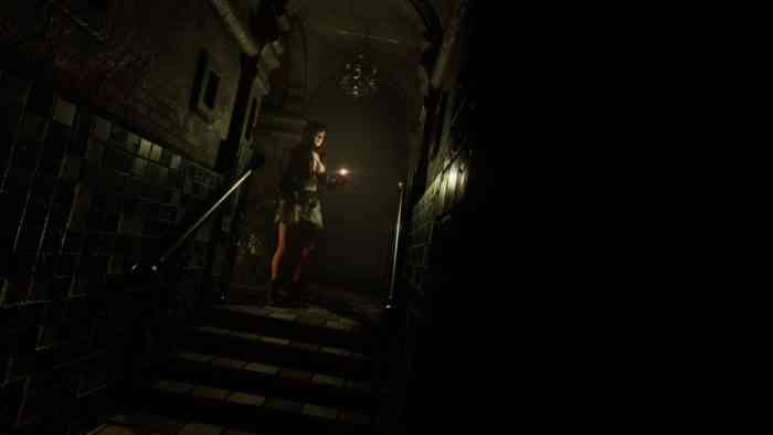 Tormented Souls protagonist Caroline Walker standing at the top of some stairs, holding a lighter.